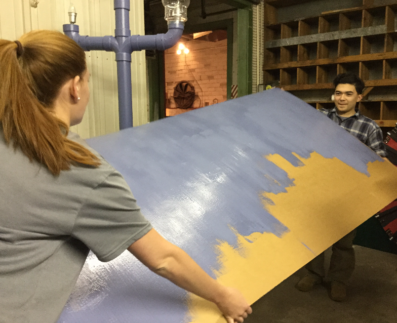 Anna Young and Jimmy Fortner flip over a prop to paint.