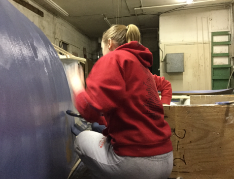 Madison Shandy painting a prop for prom construction night.