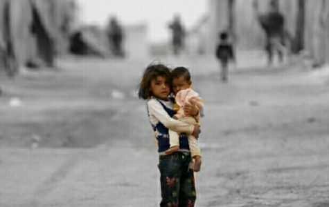 A girl carries a child in the harsh Refugee Camp.
