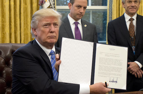 WASHINGTON, DC - JANUARY 23:  (AFP OUT) U.S. President Donald Trump shows the Executive Order withdrawing the US from the Trans-Pacific Partnership (TPP) after signing it in the Oval Office of the White House in Washington, DC on Monday, January 23, 2017.  The other two Executive Orders concerned a US Government hiring freeze for all departments but the military, and
