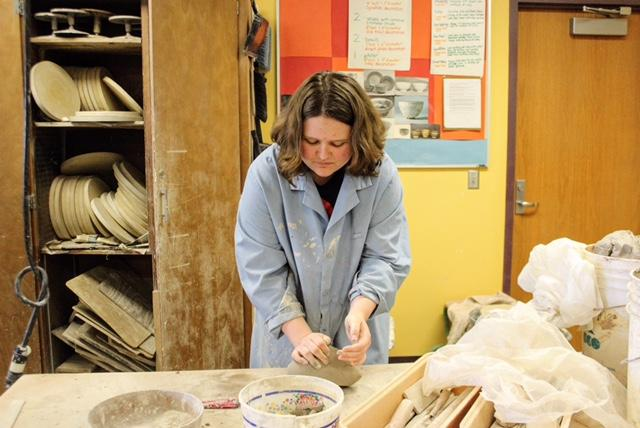 Junior+Georgia+Herrold+wedges+clay+for+her+high+school+ceramics+class.+