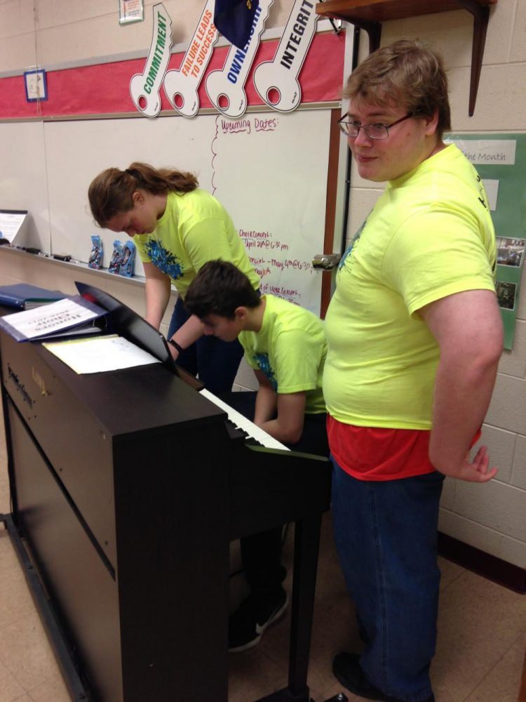 Students Megan Eisenbarth, Drake Langshaw, and Tyler Gifford playing piano at the Middle School during the Big Event.
