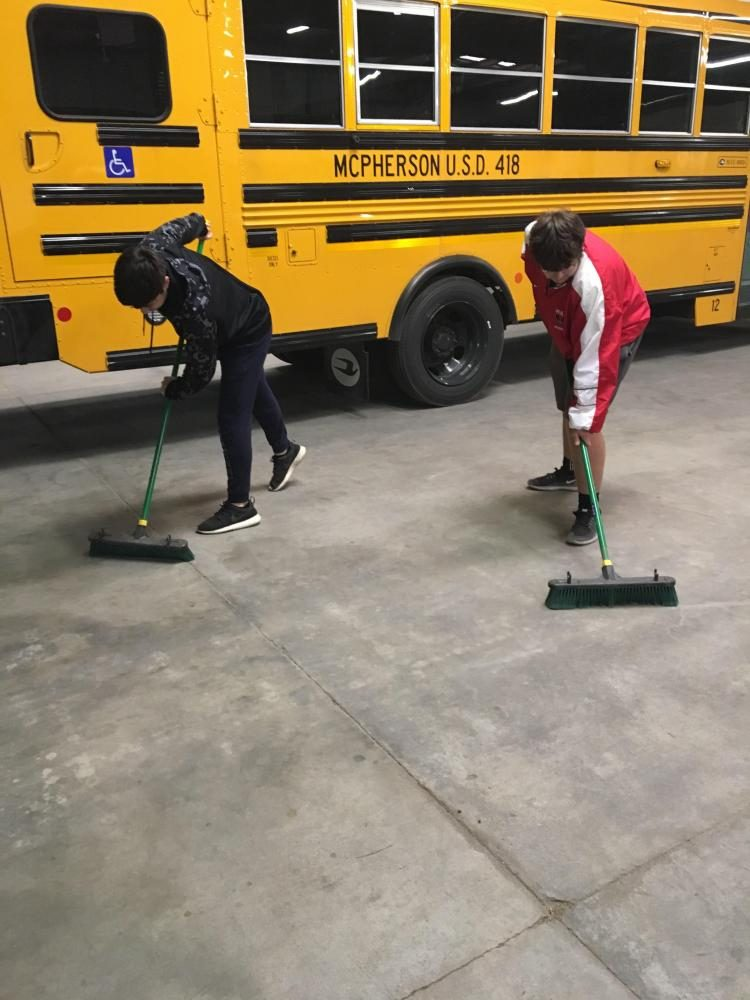 Jason Schowengerdt and Logan Hardgrave sweeping the Bus Barn for the Big Event!