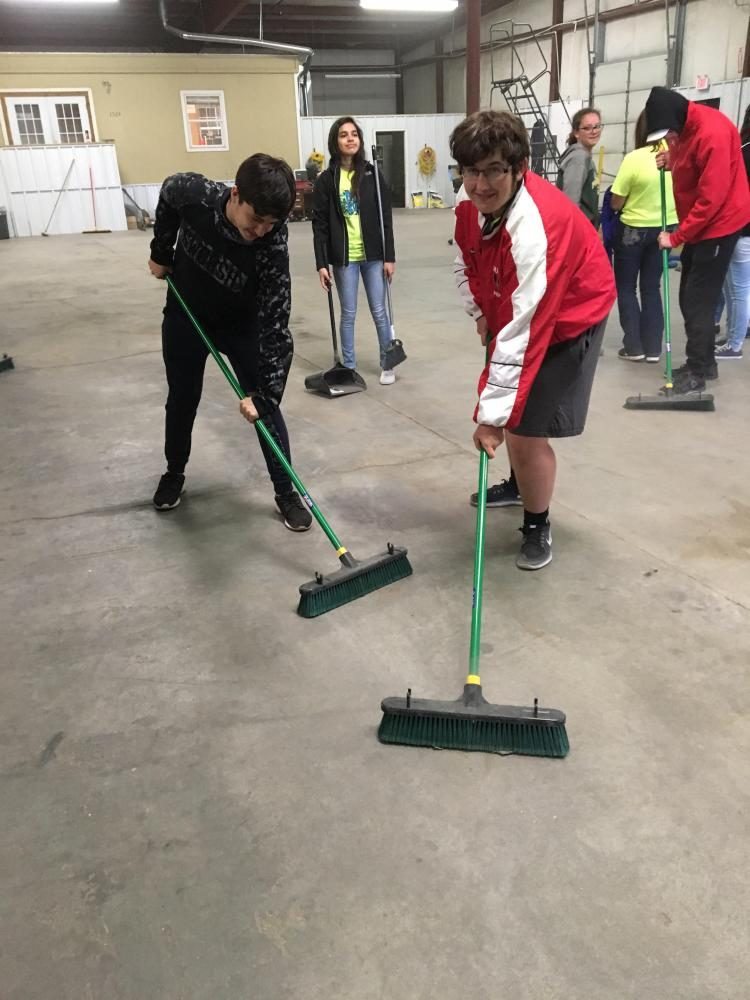 (Left to Right) Jason Schowengerdt, Aileen Santillan, Logan Hardgrave, and Kade Goss sweeping the floors of the Bus Barn during the Big Event.