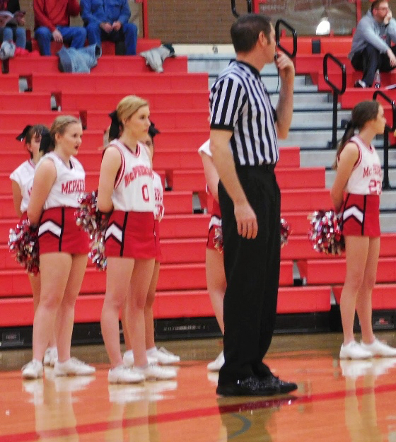The cheerleaders and ref on the sidelines on Friday nights tournament.