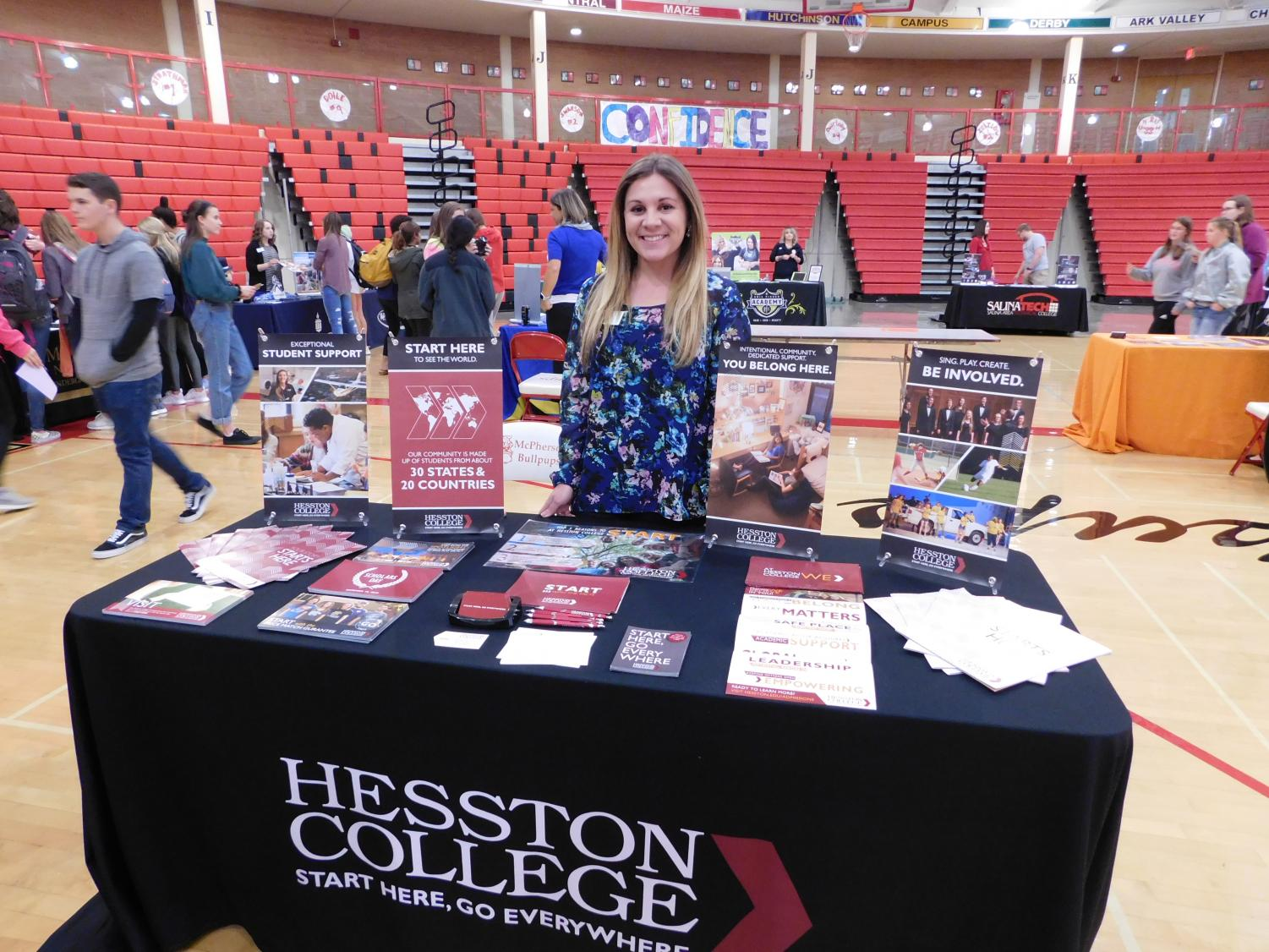 Hesston+College+representative+stands+tall+and+smiles+while+representing+her+booth.++