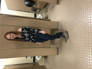 Emma Wilson is wearing an off the shoulder black shirt with jeans and grey boots