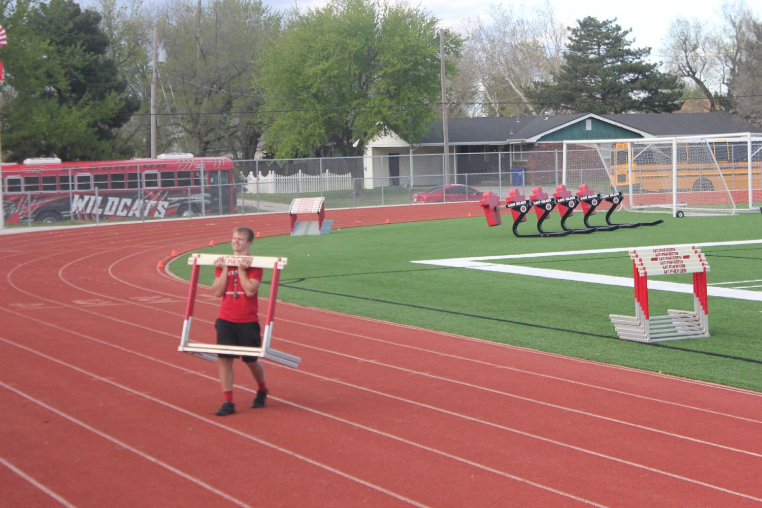 A+student+athlete+helps+move+hurtles+across+the+track+to+make+room+for+new+runners.+