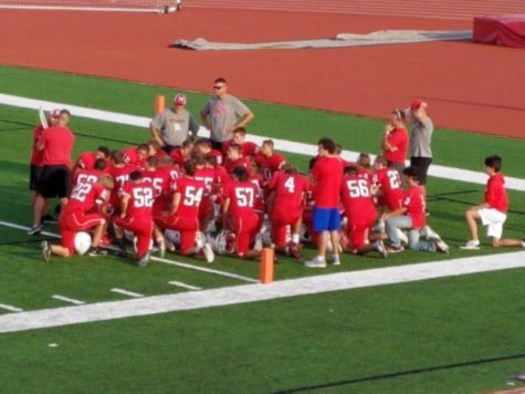 Freshman team huddle up during halftime to discuss strategies for second half of the game.