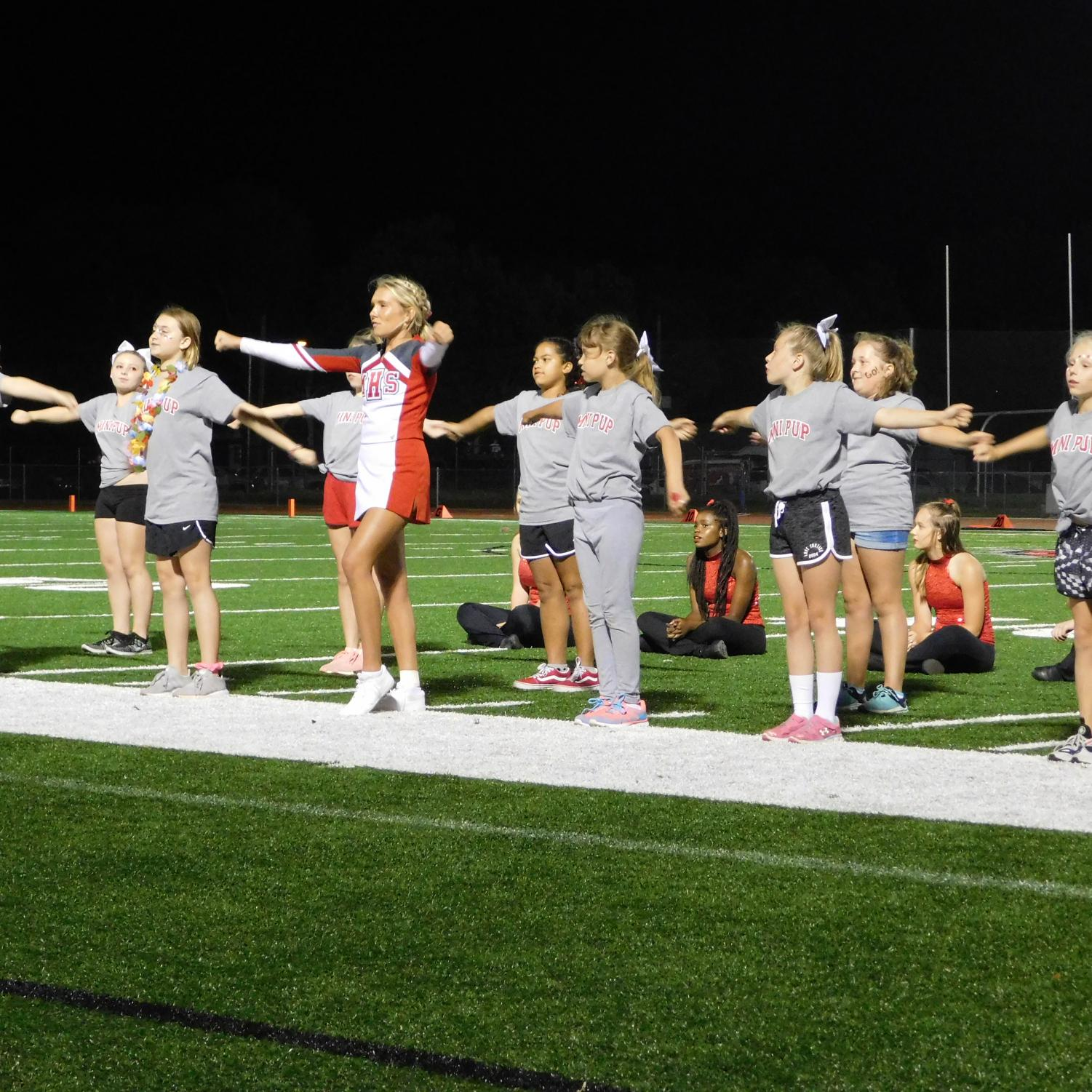 McPherson High School cheerleader,  with fifth through eighth graders, cheering to get the crowd pumped.