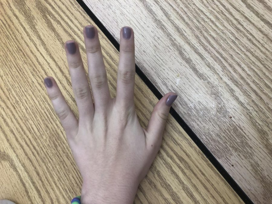 Sophomore Carly Stout ha her nails painted and does them herself rather then going to the nail salon and paying $20 for a manicure.