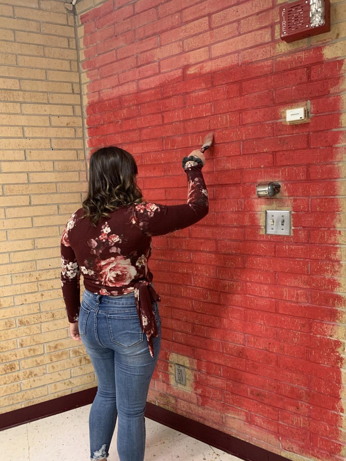 Audrey Bailey is painting the walls for the classroom