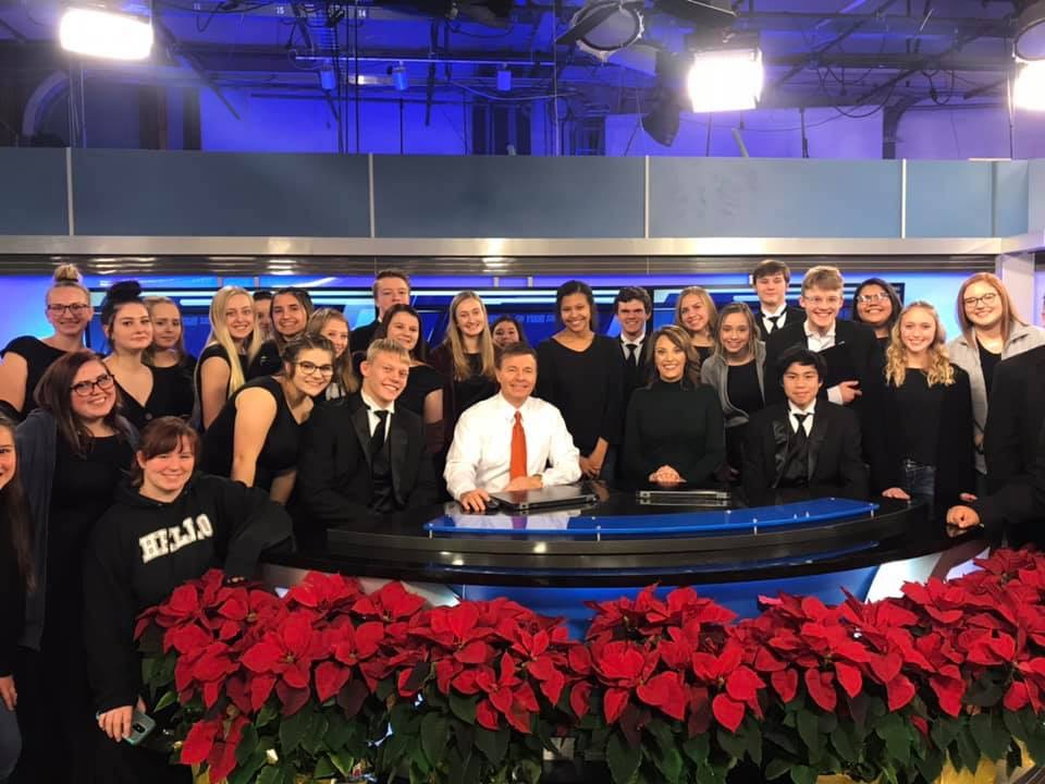 McPherson High School's Choir posing with KAKE News television hosts before pre-recording the Christmas Special.