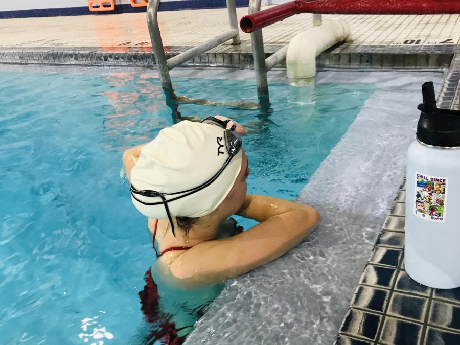 Swimmer, Mariah, takes a break to stretch.
